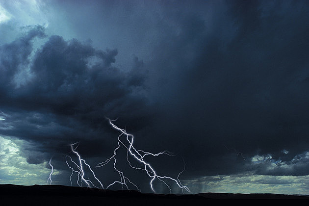 Multiple lightning bolts over rural landscape